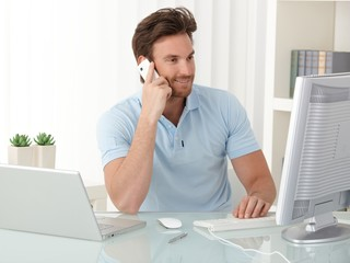 Office worker guy using computer and phone
