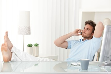 Relaxed man talking on mobile phone at desk