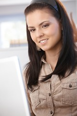 Young female browsing internet on laptop smiling