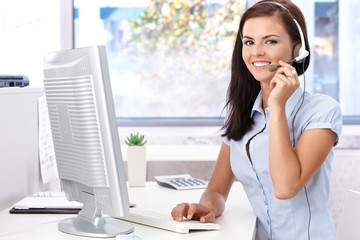 Happy female sitting at desk in bright office