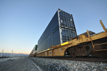 Train with stacked containers rolls by windfarm