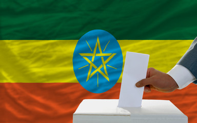 man voting on elections in ethiopia in front of flag
