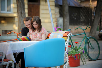 Hugging young couple in a summer cafe