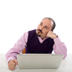 Portrait of thinking young man looking at laptop