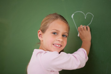 Smiling schoolgirl drawing a heart
