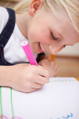 Portrait of a delighted girl drawing