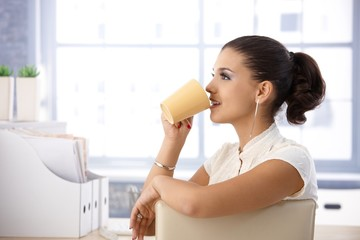 Casual office worker drinking tea in office