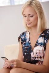 Pretty blonde texting on mobile phone