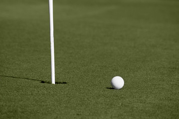 Golf ball close to hole with flagstick on putting green