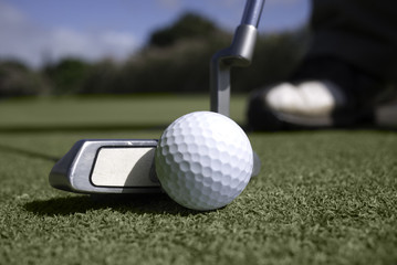 Close up of golf ball and putter on the putting green