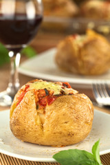 Baked potato with tomato filling and cheese on top