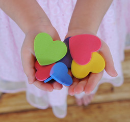 closeup of childs hands holding colorful hearts