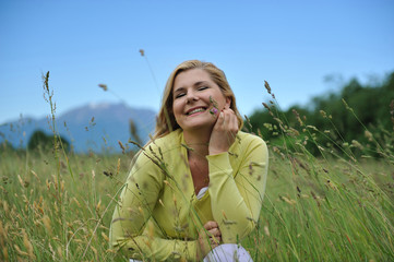 Pretty healthy summer woman outdoors on green field in Alps