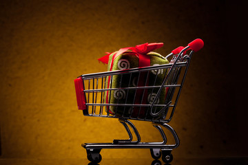 shopping cart with gift on yellow background