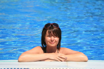 Young woman leaning on the edge of a pool