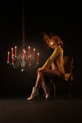 Maskierte Frau und Kerzenleuchter