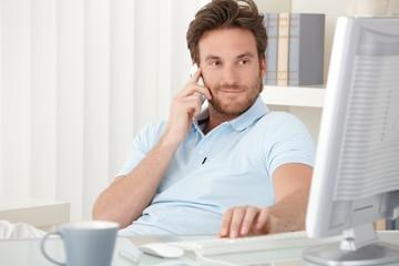 Portrait of smiling man speaking on phone