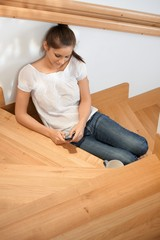 Young girl texting on stairs