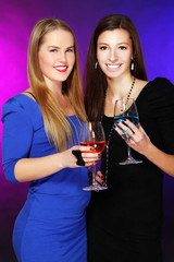 Two cheerful girlfriends with colorful cocktails