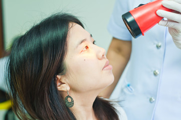 doctor shines a light into eye to check vision ocular health