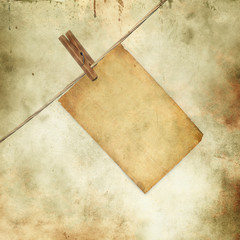 old blank paper sheet hanging on a rope on grunge background