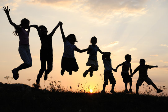 Silhouette, group of happy children playing on meadow,