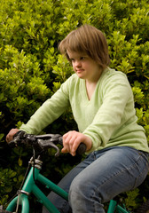 A girl with Down syndrome riding her bicycle.