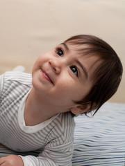 neonato con pigiama a righe che guarda verso l'alto