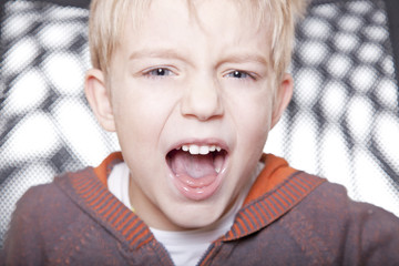 portrait of a young boy screaming and angry