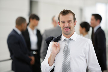 Business stood in front of colleagues with jacket over shoulder