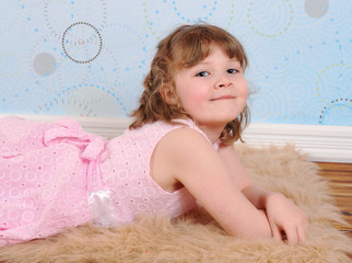 cute little girl  in dress laying on a furry brown rug