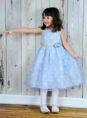 happy little girl in beautiful blue dress pointing