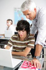 Teacher helping male pupil