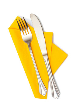 Fork and knife in a yellow cloth isolated on white