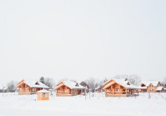the photo shows a wooden house in the snow