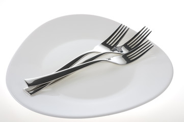 Forks on a plate  over white