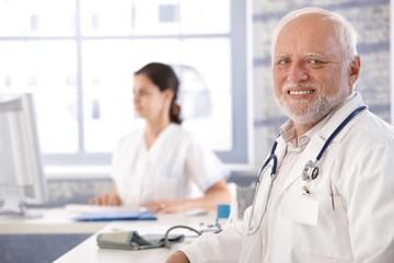 Senior doctor sitting at desk smiling