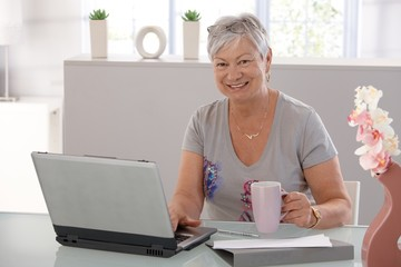 Senior woman working on laptop smiling