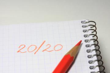 Crayon rouge sur cahier avec 20 sur 20