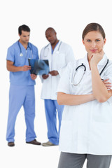 Thinking doctor with colleagues behind her