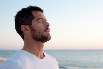 Handsome man deep breathing on the beach - fototapety na wymiar