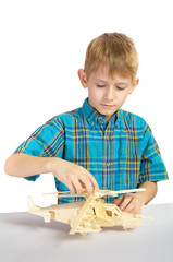 A boy builds a wooden helicopter