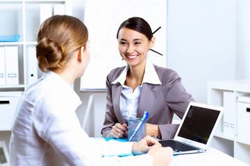 Young women in business wear working in office
