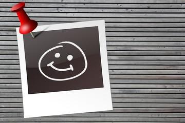 Polaroid mit Smiley auf Holzwand