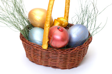 Colorful painted easter eggs in basket on white
