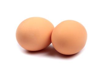 Zwei braune Eier vor weißem Hintergrund