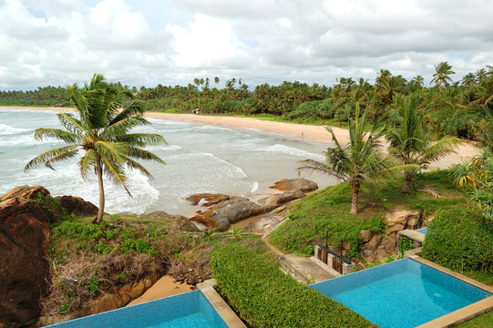Beach view swimming pools at luxury villas and turquoise water o