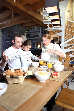 married couple and daughter having breakfast together