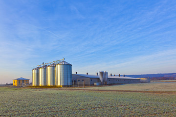 silos in the middle of a field in wintertime