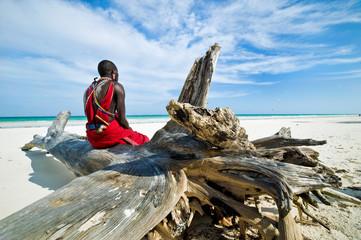Maasai sitting by the ocean on the beach Wall mural